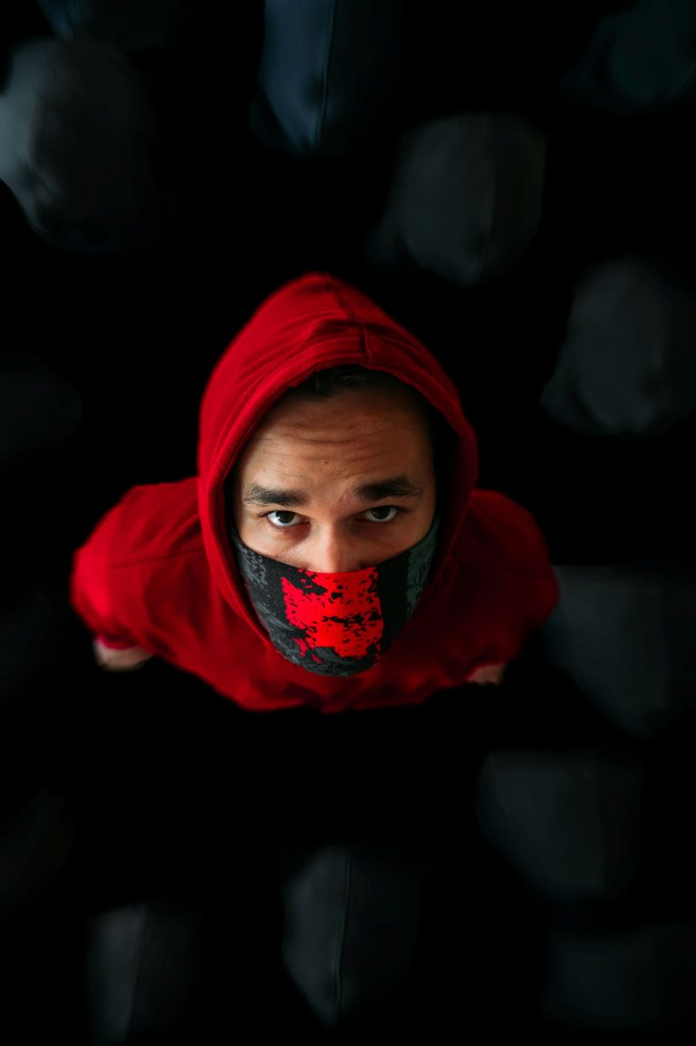 A man with red hood and mask indicating social distancing