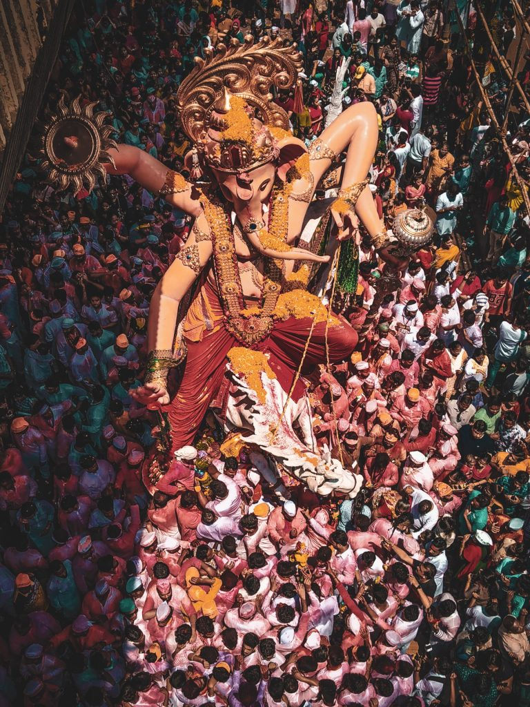 Ganesh Puja Procession with lots of people around the image
